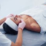 Close up view of woman that lying down in spa salon and have face cleaning procedure by cosmetologist in gloves